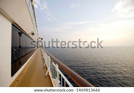 Wide angle view of cruiseship side deck and ocean in evening sunlight
