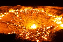 Wide angle view of Darvaza Gas Crater flames in Turkmenistan, Central Asia at night. Natural gas field intentionally set on fire by geologists. Also referred as the Door to Hell or Gates of Hell.