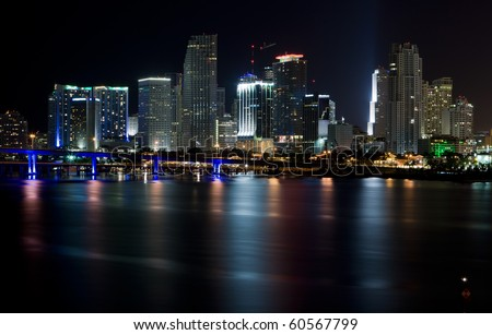 Wide angle View of Downtown Miami and Biscayne Bay in the evening with colored reflections of the skyscrapers in the bay.