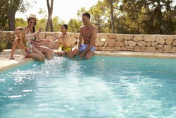 Wide Angle View Of Family On Vacation Having Fun By Pool