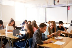 Wide Angle View Of High School Students Sitting At Desks In Classroom Using Laptops