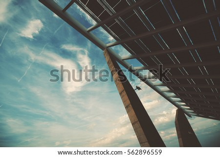 Wide angle view of modern hi-tech solar photovoltaic panel with empty space for your message on the left on sky, huge solar battery, giant energy producing structure, Barcelona, shooting from bottom #562896559