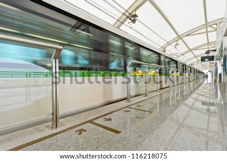 wide angle view of modern metro station with train motion