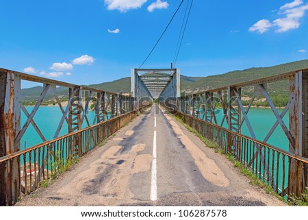 wide angle view of road and steel bridge over reservoir - stock photo