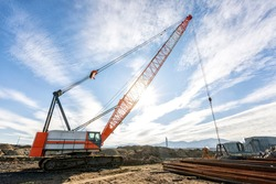 Wide angle view of the big crawler crane in the construction site. A crawler crane has its boom mounted on an undercarriage fitted with a set of crawler track that provide both stability and mobility.