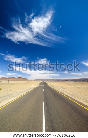 Wide angle view of the C13 road between Noordoewer and Aussenkehr near the South African Border in Namibia, Africa. The road cuts through the Aussenkehr Nature Reserve. Mountains in the background