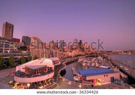 Wide angle view of the city of seattle with its tall buildings, restaurants, streets, and boats in waterfront docks