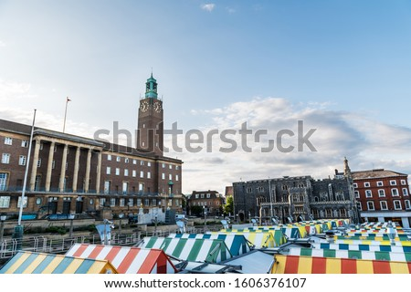 Wide-angle view of the colourful rooftops on Norwich Market, with the medieval Guildhall in the background, a historic construction originally built to serve as the seat of the city government.