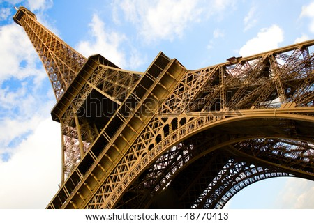 Wide angle view of the Eiffel Tower over the blue sky with clouds