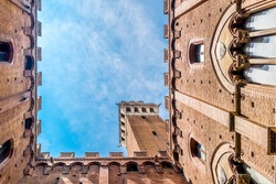 Wide angle view on the La Torre del Mangia; picture taken from the ground looking straight up;  Piazza del Campo, Palazzo Pubblico, Siena, Italy.