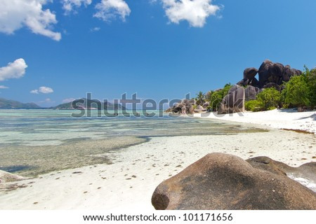 Wide angle view over Source d'Argent dream beach with tourists bathing and the famous granite rock formation in the background