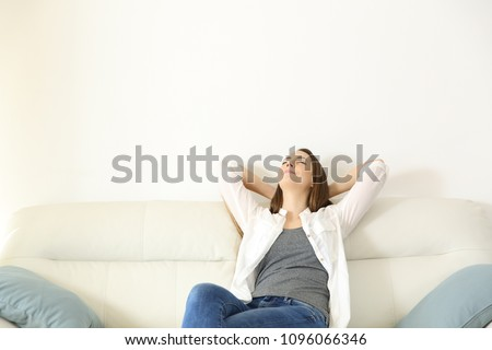 Wide angle view portrait of a woman relaxing on a couch with copy space above