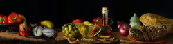 Wide angle view with a bottle of olive oil, olives, vegetables and bread in the style of the old Dutch artists