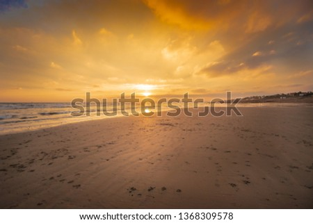 Wide angled shot of sunset on a sandy beach.