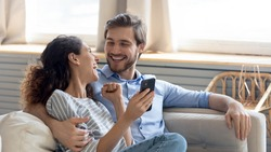 Wide banner panoramic view of overjoyed millennial couple celebrate online win on cellphone together. Happy young Caucasian man and woman triumph with good sale deal or promotion discount on cell.