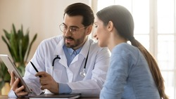 Wide banner panoramic view of young male GP use tablet discuss illness anamnesis to female patient at meeting. Man doctor and woman client look at pad screen consider test results on gadget.