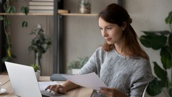 Wide banner panoramic view of young woman sit at desk at home office look at laptop screen working online with documents. Focused millennial female busy using computer considering paperwork.
