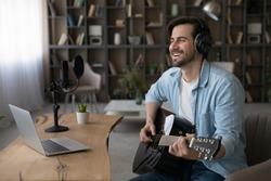Wide banner view of happy millennial male artist hold guitar take online video webcam lesson on computer. Smiling young man singer or composer use instrument watch music tutorial on laptop at home.