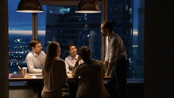 Wide banner view or African American male boss or director head meeting with diverse colleagues in office at night. Multiracial employee work late hours, manage to meet deadline. Teamwork concept.