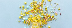 Wide banner Yellow sugar sprinkles grainy on blue background, close-up flat lay