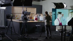 WIDE Behind the scenes of studio set, makeup artist make corrections during shooting television cooking show featuring celebrity chef, professional TV production
