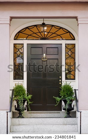 Wide Black Front Door with Surrounding Windows and Lunette and Potted Plants