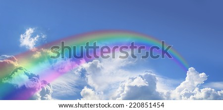 Wide blue sky with fluffy cloud formations clouds and a rainbow arcing off into the distance