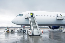Wide body aircraft with ladder stairs to the airport parking
