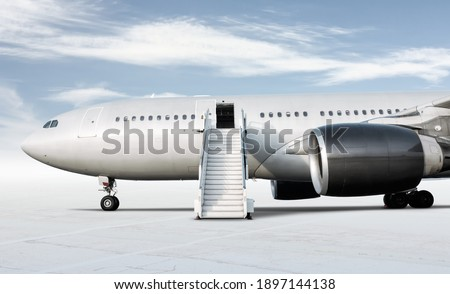 Wide body passenger airplane with a boarding steps at the airport apron isolated on bright background with sky Foto stock ©