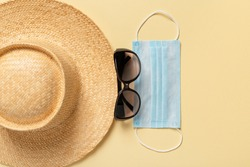Wide brim straw hat, sunglasses and blue medical face mask on a yellow background. Protection against viral infections, covid and flu during summer vacation or travel concepts. Top view.
