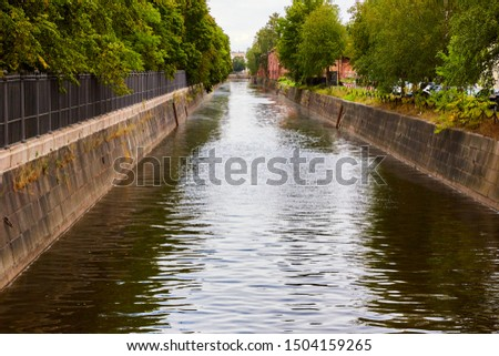 Wide canal with stone shores and a park on the shore #1504159265