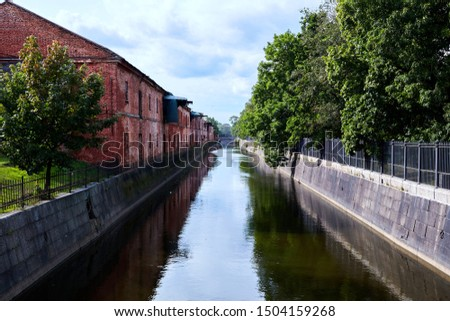 Wide canal with stone shores and a park on the shore #1504159268