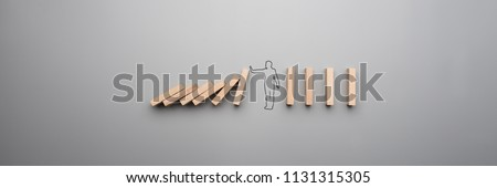 Wide cropped image of the outline of a businessman stopping the domino effect on gray background. #1131315305