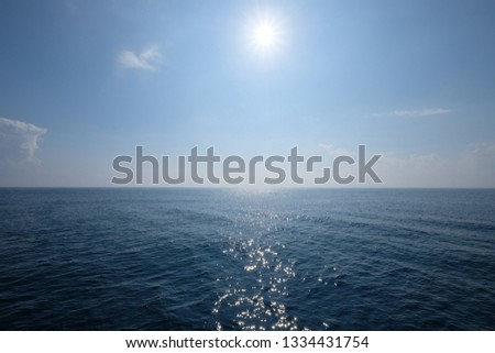 wide deep blue sea horizon. Bright sun shining in the center of blue sky. quiet peaceful ocean surface with sunlight reflection. some white cloud. simplicity. #1334431754