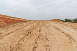 Wide dry cracked dirt uphill road perspective view