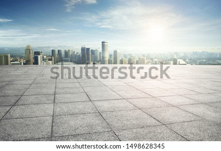 Wide empty concrete square floor with  cityscape view.
