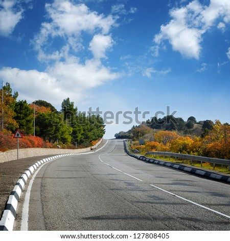 wide empty road between autumn trees and blue cloudy sky
