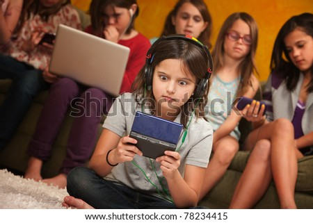 Wide-eyed little girl with headphones and game console with friends