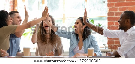Wide horizontal image multicultural cheerful businesspeople sitting together at meeting giving high five gesture feels excited happy, showing team spirit, celebrating victory goal achievement concept