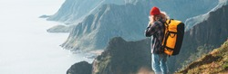 Wide image. Alone man expeditor wearing professional backpack standing on the edge cliff mountain above sea and looking on epic high landscape. Lifestyle adventure vacation