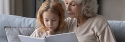 Wide image close up mature grandmother and little granddaughter reading book together, caring loving granny embracing preschool girl child, telling interesting fairytale story, children education