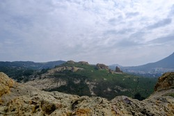 wide landscape of a mountain with hoodoo rocks and shapes on a hill with forest in a cloudy day