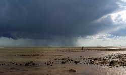 Wide landscape with an impressive storm front. Rain falls from heavy cloud in the distance as the weather sweeps across a sandy beach at low tide. A man and child look tiny as they walk towards gulls.