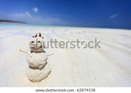Wide lens photo of funny snowman made from white tropical sand at beach