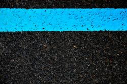 Wide light blue band painted on pitch black asphalt.