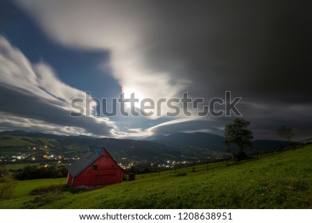 Wide mountain panorama at dusk. Small red wooden house on green grassy slope under evening gray cloudy forboding sky, bright lights of road and village down in the valley, woody hills on horizon.