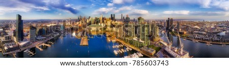 Wide panorama of Docklands modern suburb in Melbourne on Yarra river from amusement wheel to city CBD waterfront and Port Melbourne - elevated aerial view.
