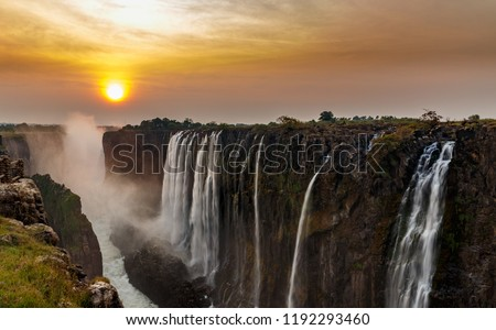 Wide panorama of dreamy victoria falls at sunset with orange sun in the horizon #1192293460