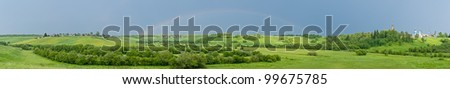 Wide panorama of hilly landscape with full rainbow in the sky, villages and church in background. - stock photo