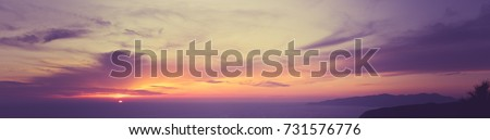 Wide panorama of sunset sky with clouds and sunlight over the sea for your idea of web header. Cloudy landscape for background in serenity colors - blue, ultra violet, yellow and pink tone.